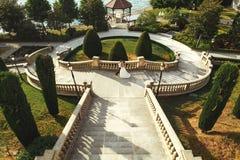 Красивая невеста обнимая красивый groom на каменных лестницах приближает к морю Стоковое Изображение RF