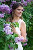 Красивая невеста представляя около зацветая дерева сирени Стоковая Фотография RF