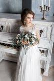 Красивая невеста с букетом около белого рояля Стоковая Фотография