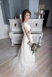 Красивая невеста с букетом около белого рояля Стоковые Фотографии RF