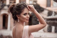Красивая невеста с ювелирными изделиями серег жемчуга носит розовое платье выпускного вечера На открытом воздухе романтичный порт стоковое фото rf