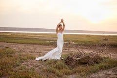 Красивая невеста усмехаясь и представляя около мертвого дерева в поле Стоковые Изображения
