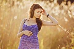 Красивая нежная беременная женщина усмехается и наслаждается солнечным летом Стоковое Изображение