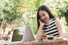 Красивая независимая работа женщины 2 с компьтер-книжкой и smartphone внутри стоковое изображение