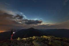 Красивая ноча лета в горах Профилируйте силуэт молодого туристского человека hiker при электрофонарь стоя самостоятельно на скали стоковое изображение