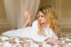Красивая обольстительная женщина flirting при камера лежа на кровати при в белый купальный халат смотря вверх с кокетливым Стоковое Фото