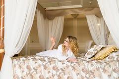 Красивая обольстительная женщина flirting при камера лежа на кровати при в белый купальный халат смотря вверх с кокетливым Стоковые Изображения