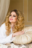 Красивая обольстительная женщина flirting при камера лежа на кровати при в белый купальный халат смотря вверх с кокетливым Стоковое Изображение