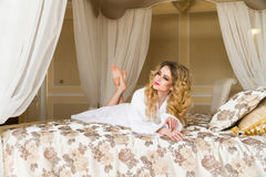 Красивая обольстительная женщина flirting при камера лежа на кровати при в белый купальный халат смотря вверх с кокетливым Стоковые Фото