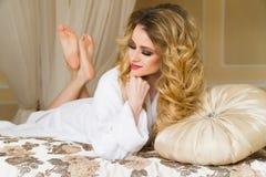 Красивая обольстительная женщина flirting при камера лежа на кровати при в белый купальный халат смотря вверх с кокетливым Стоковые Фотографии RF