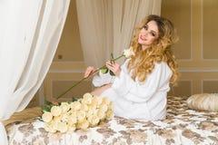 Красивая обольстительная женщина flirting с камерой сидит на кровати с большим букетом белых роз в белизне Стоковое Изображение RF