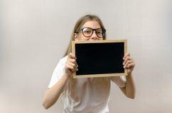 Красивая озорная девушка со стеклами держа знак внутри ее руки экземпляр-космос стоковое фото