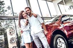 Красивая пара держит ключ их нового автомобиля, смотрящ камеру и усмехаться стоковые фото
