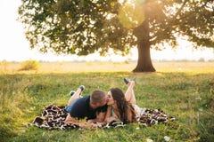Красивая пара отдыхает вне города, сидя около большого дерева в саде любовная история девушки сада мальчика целуя Стоковая Фотография