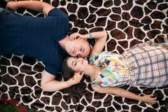 Красивая пара отдыхает вне города, сидя около большого дерева в саде любовная история девушки сада мальчика целуя Стоковое фото RF