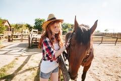 Красивая пастушка женщины позаботить о ее лошадь на ферме Стоковое Фото
