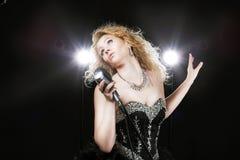 Красивая певица девушки в черном платье с микрофоном Стоковые Фото
