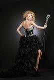 Красивая певица девушки в черном платье с микрофоном Стоковая Фотография