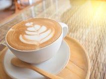 Красивая пена в кофейной чашке на таблице с светом солнца стоковые изображения rf