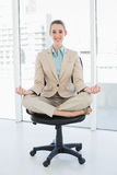 Красивая первоклассная женщина сидя в положении лотоса на ее вращающееся кресло Стоковые Изображения