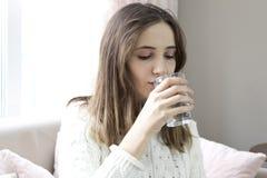 Красивая питьевая вода молодой женщины стоковые изображения rf