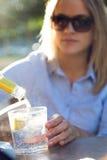 Красивая питьевая сода молодой женщины в террасе ресторана стоковая фотография