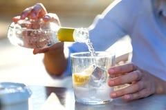 Красивая питьевая сода молодой женщины в террасе ресторана стоковая фотография rf