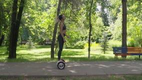 Красивая подходящая женщина на hoverboard идя в парк акции видеоматериалы