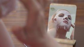 Красивая пожилая женщина в лицевой маске для стороны Косметическая забота кожи процедуры Концентрация эмоции выбора r сток-видео