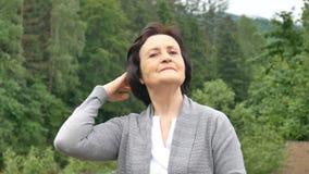 Красивая пожилая женщина против фона леса горы выправляет ее волосы с ее рукой Пенсионеры сток-видео