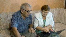Красивая пожилая пара учит работать на компьтер-книжке видеоматериал