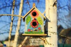 Красивая покрашенная смертная казнь через повешение birdhouse дома птицы на дереве березы внутри Стоковая Фотография