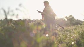 Красивая полная женщина кося траву с косой на зеленом поле лета Фольклор, традиции Работа в акции видеоматериалы