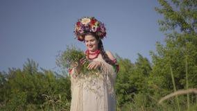 Красивая полная женщина с венком на ее цветках обнюхивать головы на зеленом поле лета, тогда бег после человека сток-видео