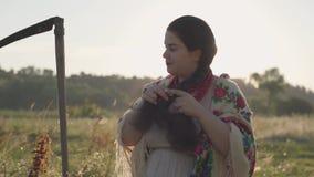 Красивая полная женщина с косой заплетая ее волосы в солнечном свете на зеленом поле лета Фольклор, традиции акции видеоматериалы