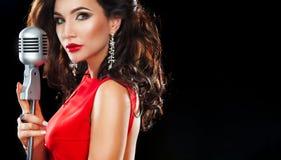 Красивая поя девушка в клубе караоке Женщина красоты с микрофоном Стоковая Фотография RF