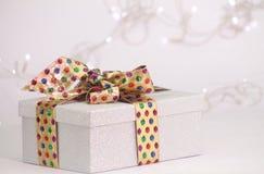 Красивая подарочная коробка в сияющем материале с золотой лентой Стоковая Фотография