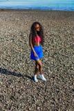 Красивая подростковая черная девушка в голубой юбке и розовый бюстгальтер на r Стоковое Изображение RF