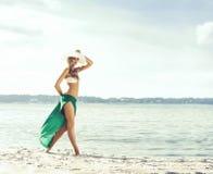Красивая, подходящая женщина при совершенные ноги представляя на пляже в gr Стоковое Изображение
