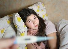 Красивая предназначенная для подростков девушка с длинным больным темных волос в кровати Стоковые Фотографии RF