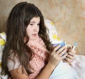 Красивая предназначенная для подростков девушка с длинным больным темных волос в кровати Стоковые Изображения RF
