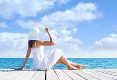 Красивая, привлекательная модель представляя в белом платье на деревянной пристани Предпосылка моря и неба Каникулы, путешествуя  стоковое изображение rf