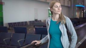 Красивая привлекательная женщина в крупном аэропорте Ждать полет Используя travolator, смотря вокруг акции видеоматериалы