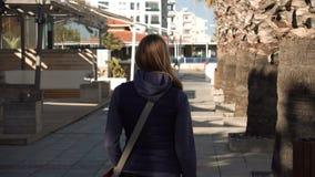 Красивая привлекательная женщина идя вниз с улицы, солнце, тени От позади С курорта сезона акции видеоматериалы