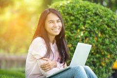 Красивая работница дела используя Iphone Ipad пока работающ с компьтер-книжкой Стоковое Фото