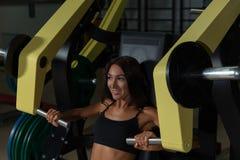 Красивая разминка девушки на машине тренировки в спортзале спорта Стоковое Изображение