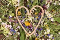 Красивая рамка в форме сердца сделанного из веревочки лежа на wildflowers Стоковое Изображение RF