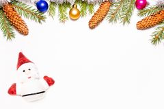 Красивая рамка рождества сделанная из ветвей ели, конусов и multicolor игрушек украшенных с Санта Клаусом изолировала на белой пр стоковые изображения rf