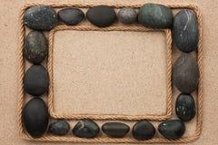 Красивая рамка с веревочкой и черные камни на песке Стоковое Изображение RF