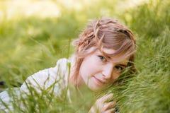 Красивая расслабленная молодая женщина лежа на траве стоковые фотографии rf